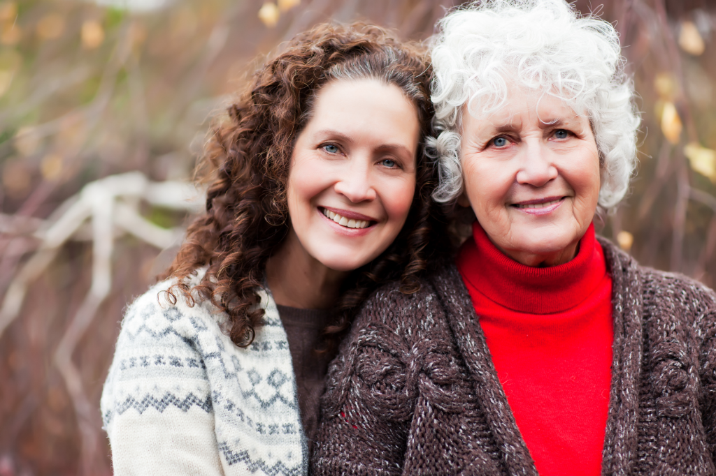 Senior woman and adult daughter pose for photo