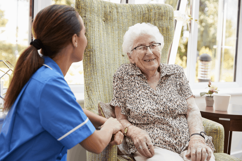 Senior woman in memory care laughs with caregiver