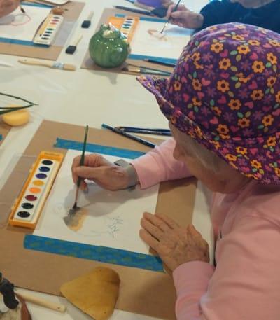 woman at residences senior living painting