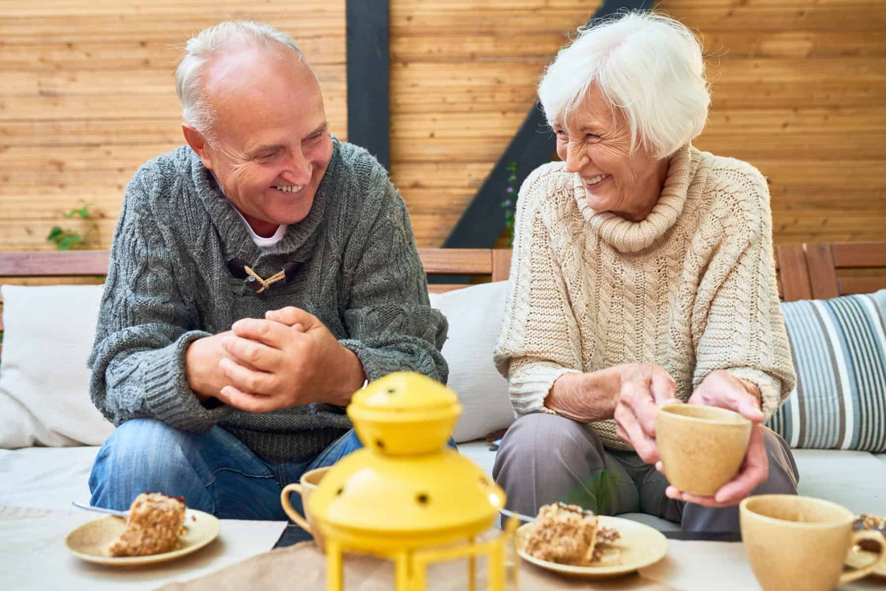 Portrait of happy senior couple laughing heartily enjoying time together in retirement sitting at table in outdoor cafe drinking coffee with cakes