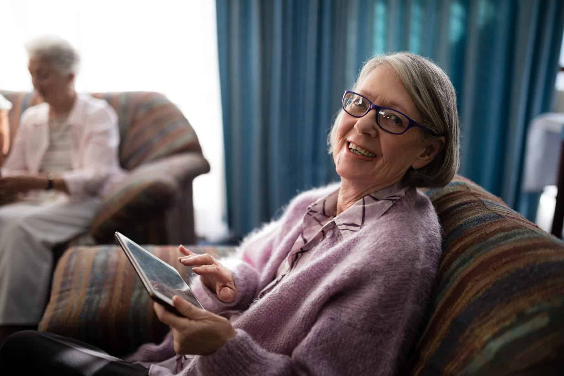 Portrait of smiling senior woman sitting with digital tablet on armchair at retirement home