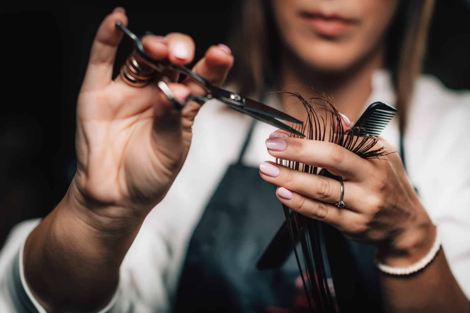 Close-up of a hairdresser cutting woman's hair.