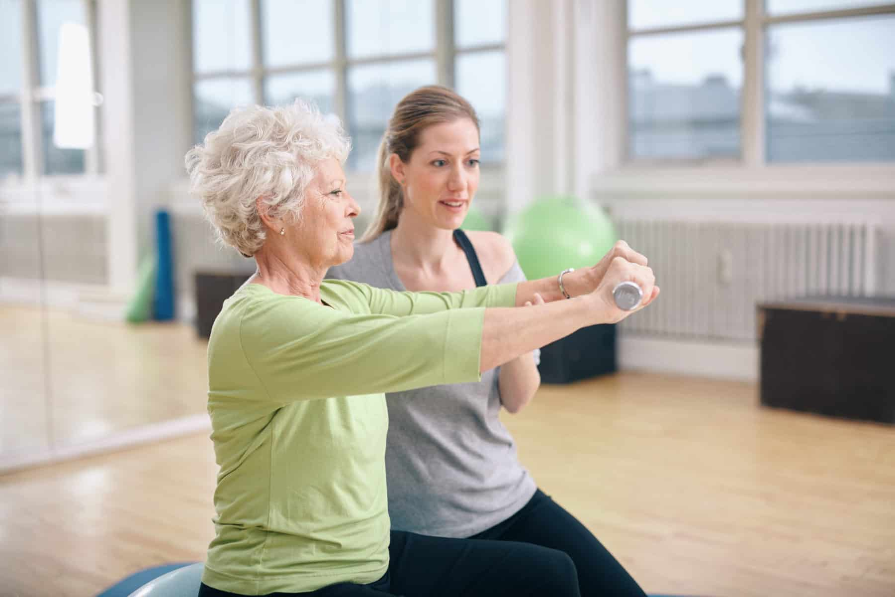 Senior woman being assisted by instructor in lifting dumbbells at gym. Senior woman training in the gym with a personal trainer at rehab.