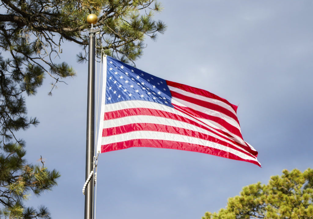 American flag blowing in the wind in a park, selective focus.