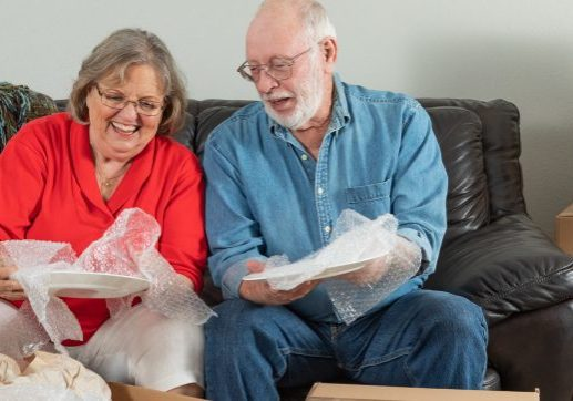 Senior Adult Couple Packing or Unpacking Moving Boxes.