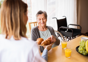Caregiver helps senior woman with dementia at mealtime