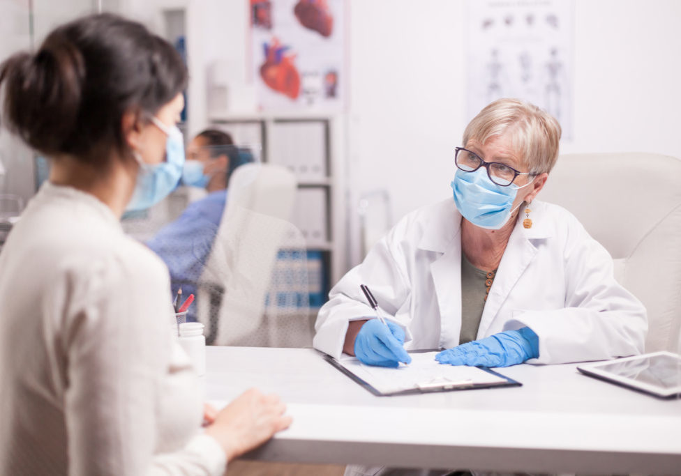 Doctor wearing protection mask against covid taking notes during consultation with patient in medical clinic. Nurse wearing blue uniform while working on computer.