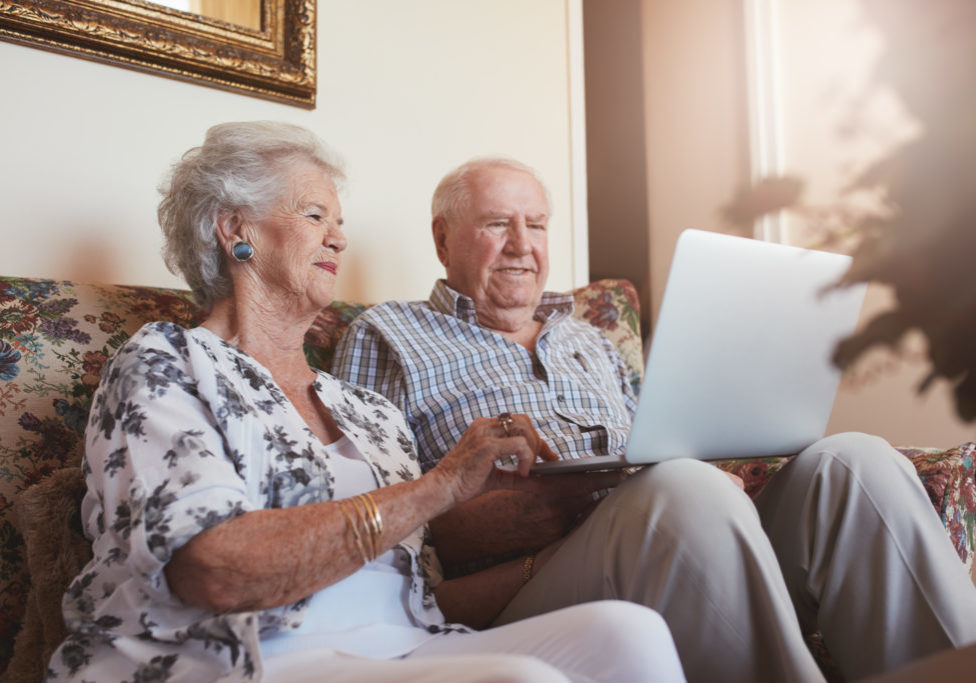 Elderly couple using laptop computer at home. Senior man and woman sitting on sofa working on laptop.