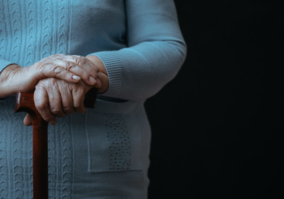 Old person with walking stick, black background, close up