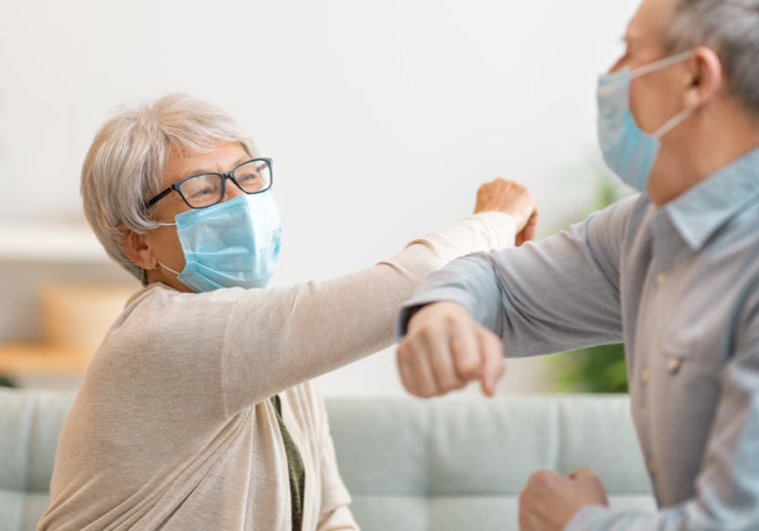 Senior couple wearing face masks and greeting bumping elbows during coronavirus and flu outbreak. Virus and illness protection, home quarantine. COVID-2019.